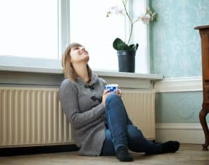 Woman leaning back on radiator keeping warm - renewable heating from Greenscape Energy